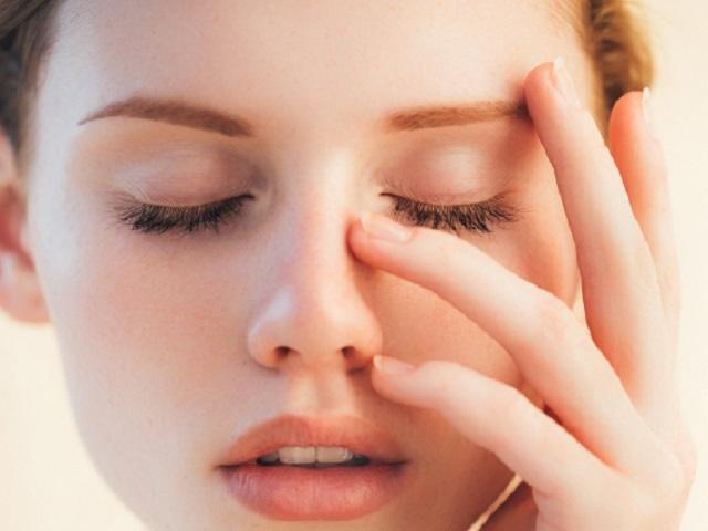 顔を押さえる若い女性