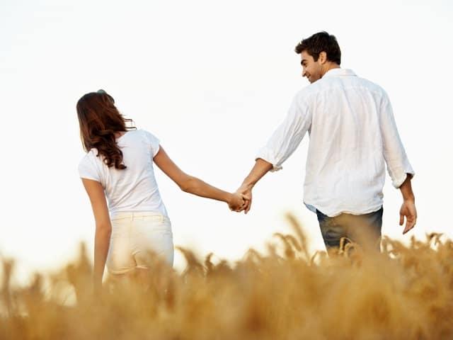 草原で手を繋ぎ歩くカップル