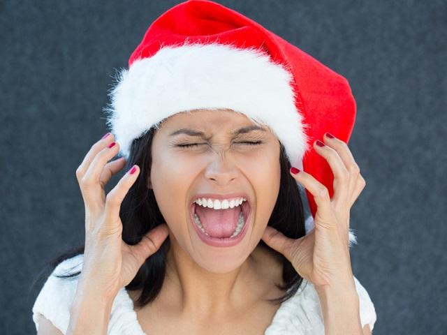 耳を覆い顔をしかめる女性