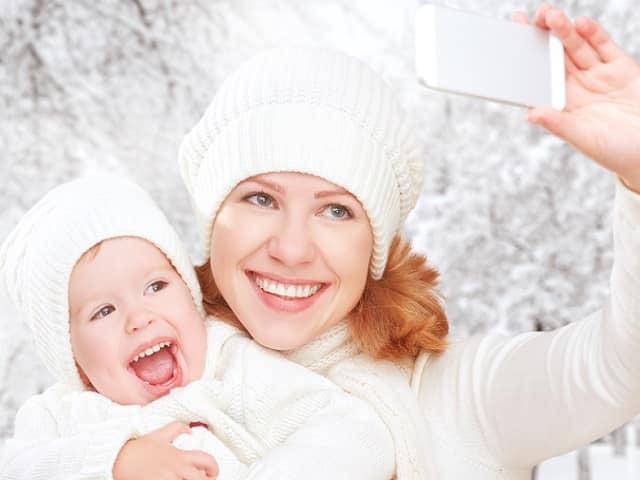 赤ちゃんと一緒に写真を撮る女性