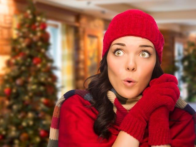 クリスマスツリーの前で驚く女性