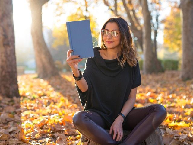 落ち葉の中で読書をする女性