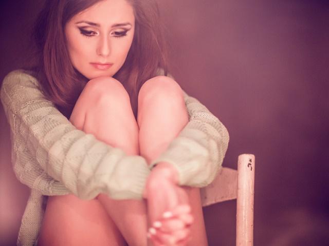 ひとりで膝を抱えこむ女性