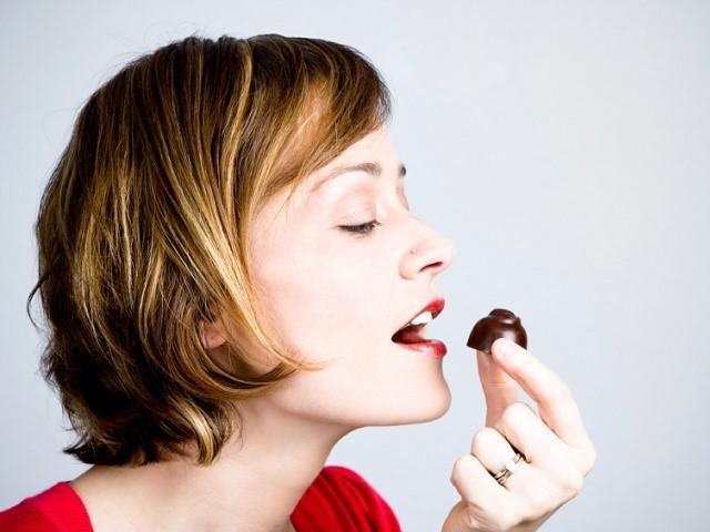 チョコを口に運ぶ女性