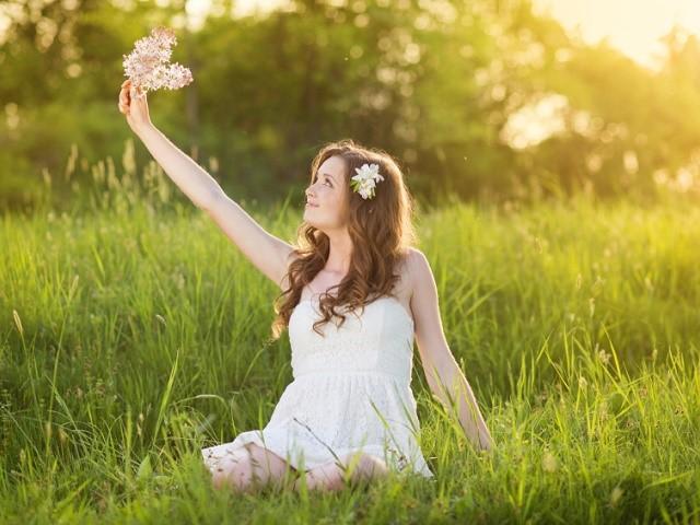 草原で花をめでる女性