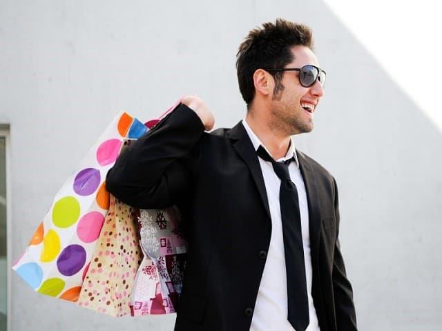 買物袋をたくさん持つスーツ姿の男性