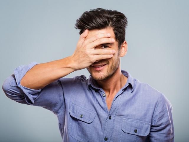 手で顔を隠すシャイな男性