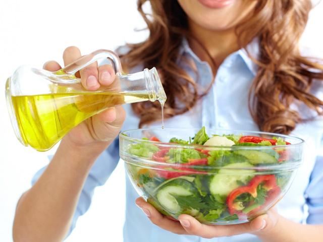 サラダにオイルをかける女性