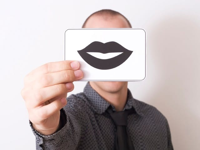 唇のカードを見せる男性