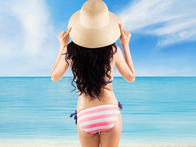 水着を着て海を見つめる女性