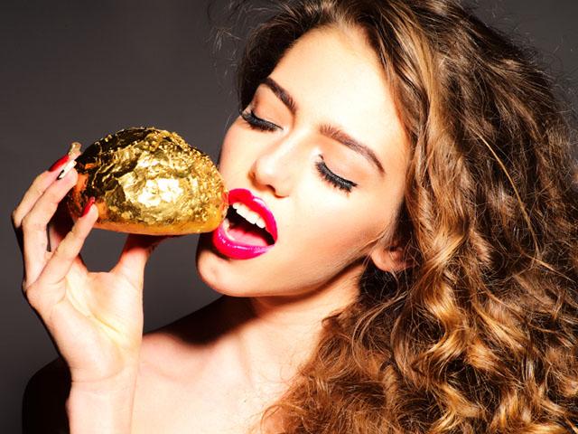 金の食べ物を頬張る女性
