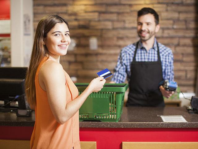 男性店員から買い物する女性