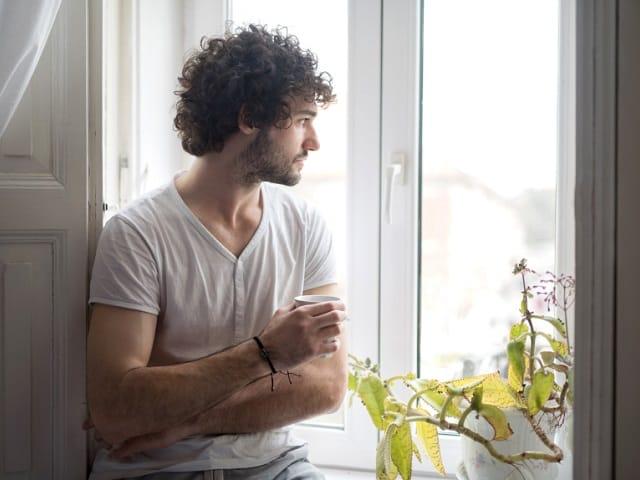 窓際にたたずむ男性