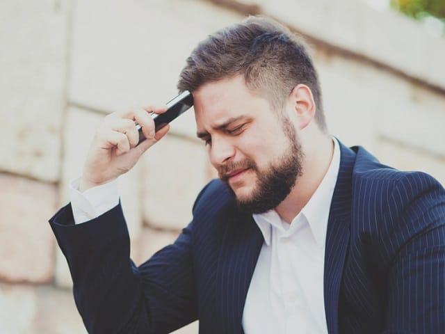 スマホで頭を抑える男性