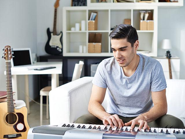 部屋でピアノを弾く男性