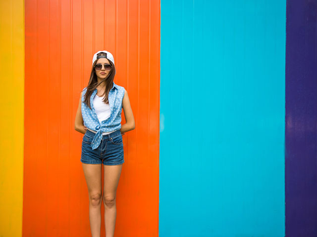 カラフルな壁の前に立つ女性
