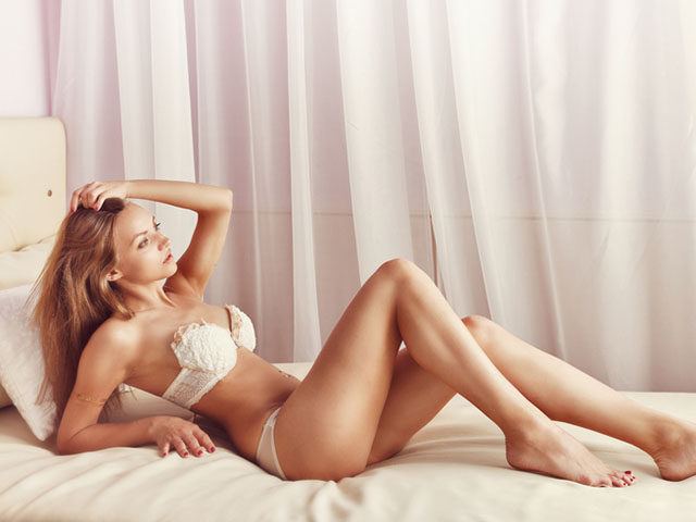 ベッドに座るセクシーな女性